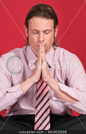 Businessman with hands clasped stock photo, Close-up of a businessman with hands clasped and eyes closed in prayer posture by Tyler Olson