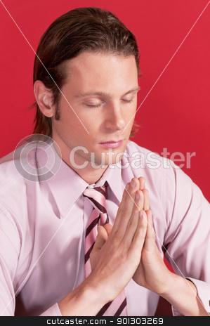 Closeup of a businessman in prayer posture stock photo, Closeup of a businessman with hands clasped and eyes closed in prayer posture by Tyler Olson