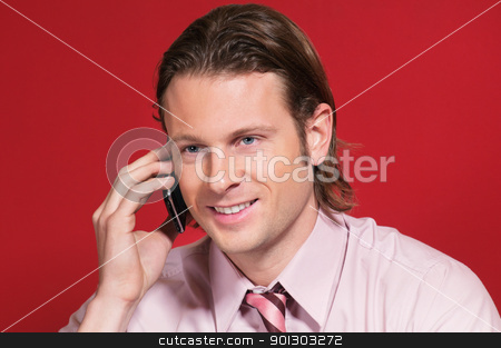 Businessman talking on a cell phone stock photo, Happy businessman talking on a mobile phone against colored background by Tyler Olson
