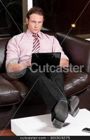Smart businessman working on laptop stock photo, Portrait of a smart businessman working on laptop with cellphone on table by Tyler Olson