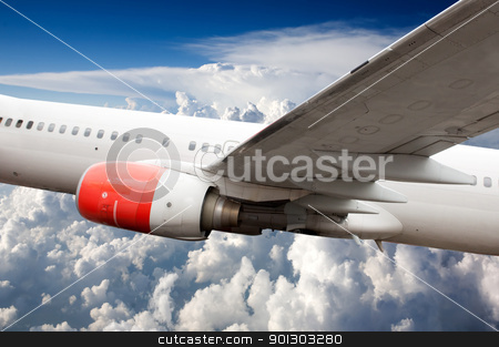 Airplane in Flight stock photo, A large commercial passenger airplane in flight over clouds by Tyler Olson