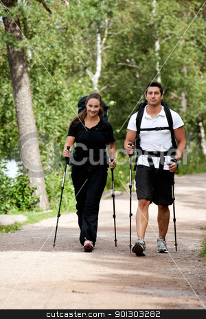 Camping Couple stock photo, A male and female camping in the woods walking on a path by Tyler Olson