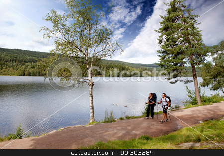Camping by Lake stock photo, A man and woman on a hike by a lake by Tyler Olson