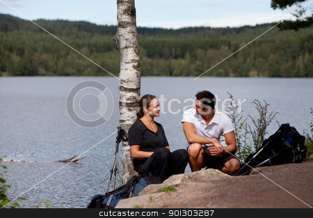 Camping Rest stock photo, A man and woman taking a break while on a camping hike by Tyler Olson