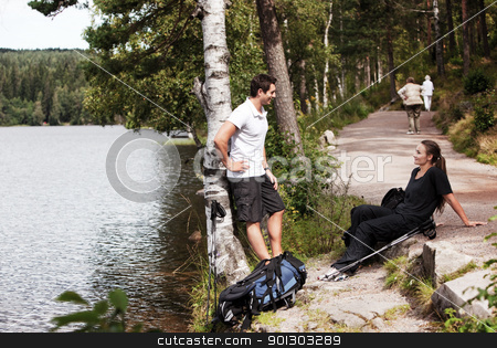 Hiking Couple stock photo, A couple hiking in the woods taking a break by the lake by Tyler Olson
