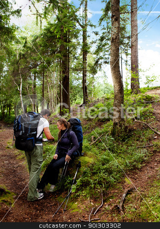 Camping Couple stock photo, A couple backpack camping in the forest looking at a map by Tyler Olson