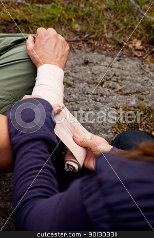 Arm Bandage stock photo, A woman applying an arm bandage on a male camper - focus on male face by Tyler Olson