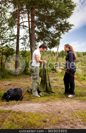 Setting up Tent stock photo, Camping lifestyle - a man and woman setting up a tent by a lake by Tyler Olson