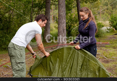 Camping with Tent stock photo, A man and woman setting up a tent in the forest by Tyler Olson