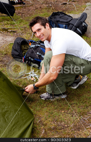 Camping Portrait stock photo, A man setting up a tent on a camping trip by Tyler Olson