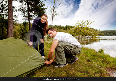 Camping Man and Woman stock photo, A man and woman camping - setting up a tent by Tyler Olson
