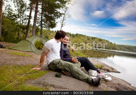 Man and Woman Camping stock photo, A man and woman happy camping in the forest by a lake by Tyler Olson