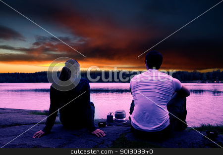 Camping Sunset stock photo, A couple watching the sunset while camping by a lake by Tyler Olson