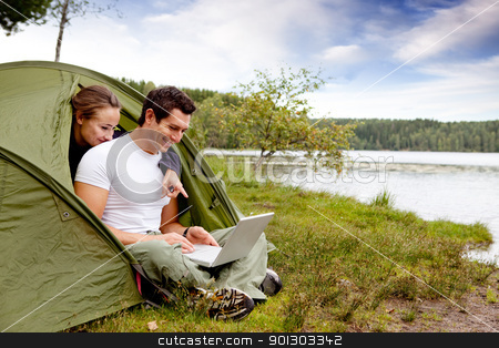 Camping Computer stock photo, A couple looking at a computer while camping in a tent by Tyler Olson