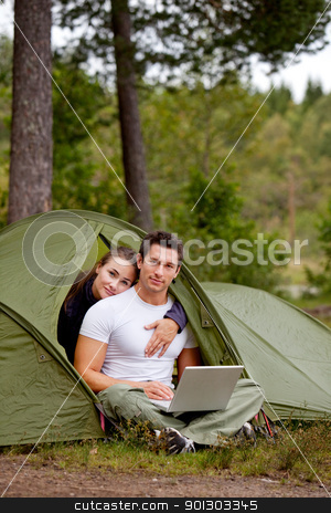 Camping Modern stock photo, A couple using a computer while camping by Tyler Olson
