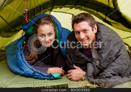 Happy Couple in Tent stock photo, A happy couple in a tent looking at the camera by Tyler Olson