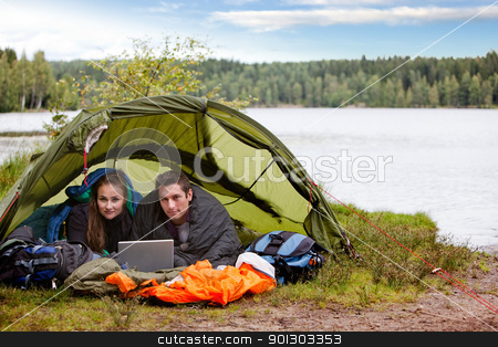 Camping with Laptop by Lake stock photo, A young couple camping with a laptop near a forest and lake by Tyler Olson