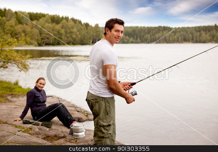 Fishing on Camping Trip stock photo, A man fishing on a lake with camping equipment and woman in background by Tyler Olson