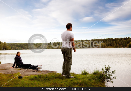 Fishing Man stock photo, A man fishing on a forest lake with woman in the background by Tyler Olson