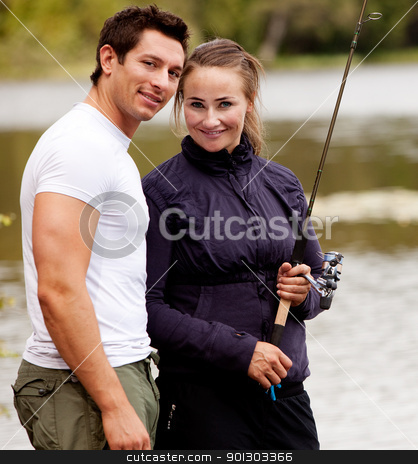 Fishing Portrait stock photo, A happy camping couple in the forest fishing by Tyler Olson
