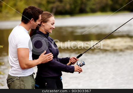 Happy Fishing Woman stock photo, A woman fishing on a interior forest lake by Tyler Olson
