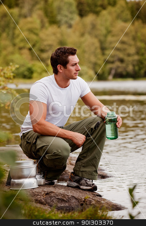 Man Getting Water stock photo, A man getting water on a camping trip in the forest by Tyler Olson