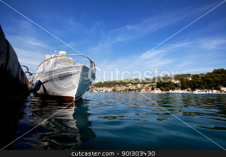 Boat at Dock stock photo, A wooden bat tied to a stone dock in old town Rab, Croatia by Tyler Olson