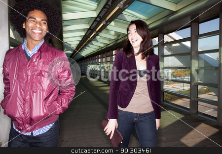 Joke Fun Couple stock photo, Two young people walking and joking in an urban setting - sharp focus on male by Tyler Olson