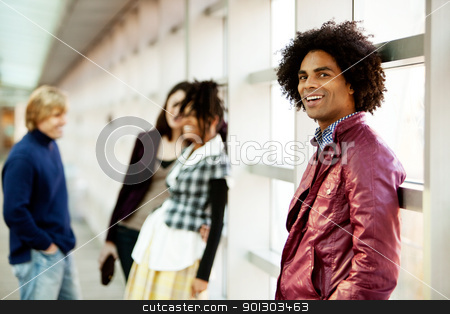 African American Man stock photo, A young African American man with a group of people in the background by Tyler Olson