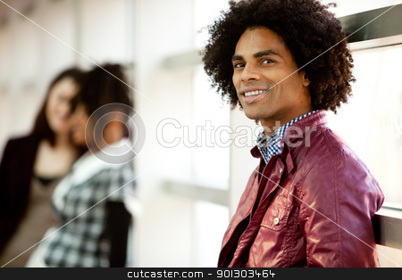 Handsome African American Male stock photo, An African American male with two women talking in the background by Tyler Olson