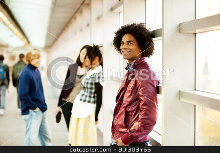 Handsome African American Male stock photo, An African American male with friends talking in the background by Tyler Olson