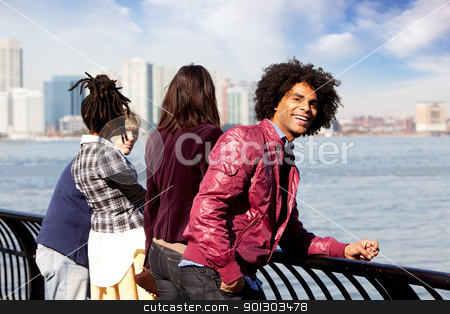 African American stock photo, An African American looking at the camera with a group of friends in the background by Tyler Olson