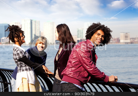 City Friends stock photo, A group of friends in the city - overlooking a harbor and skyline by Tyler Olson