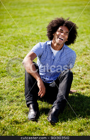 Natural Laugh stock photo, An African American sitting on grass with a natural laugh by Tyler Olson