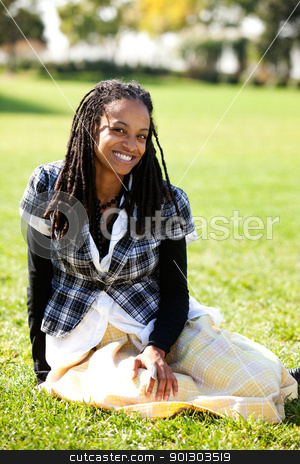 African American Student stock photo, A young African American student sitting on grass by Tyler Olson