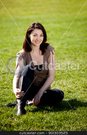 Happy Pretty Girl stock photo, A pretty female isolated on a background of grass in a park by Tyler Olson