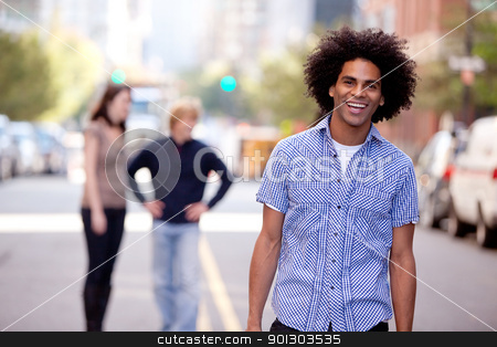 Happy African American Man stock photo, A happy young adult in a city setting with friends by Tyler Olson