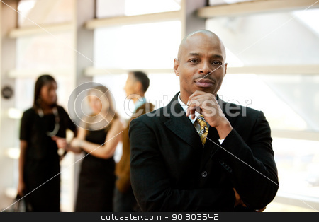 Business Man stock photo, An African American business man with co-workers in the background by Tyler Olson