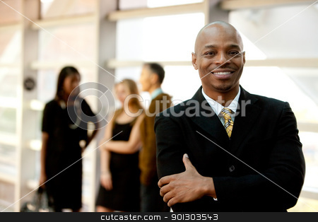Happy Black Businessman stock photo, A happy black business man with people in the background by Tyler Olson