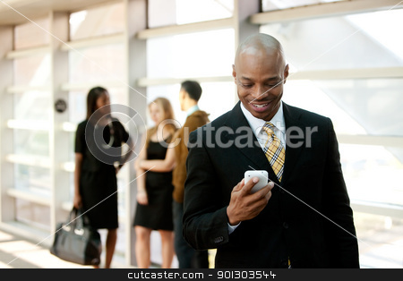 Business Man with Smart Phone stock photo, A business man with a smart phone and co-workers in the background by Tyler Olson