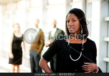African American Business Woman stock photo, An african american business woman with colleagues in the background by Tyler Olson