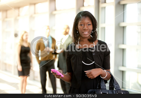 Business Woman with Smart Phone stock photo, A business woman with a smart phone with colleagues in the background by Tyler Olson