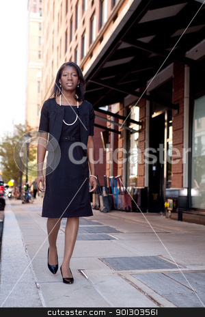 Business Woman on Street stock photo, An African American business woman walking down the street by Tyler Olson