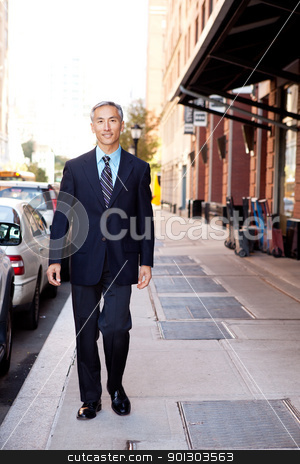 Business Man stock photo, An asian looking business man walking in a street by Tyler Olson
