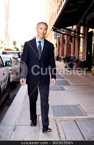 Business Man on Street stock photo, An asian looking business man walking in a street by Tyler Olson