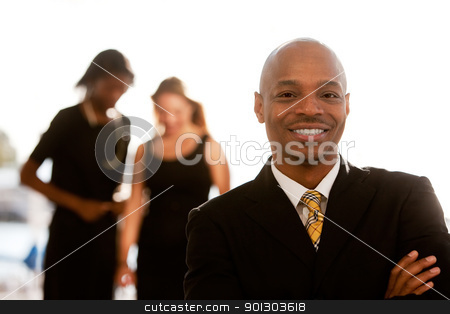 Business Man stock photo, An african american business man with colleagues in the background by Tyler Olson