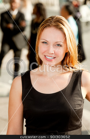 Business Woman stock photo, A business woman with coworkers in the background by Tyler Olson