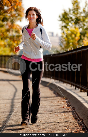 Jogging stock photo, A young woman jogging on a path in a park by Tyler Olson