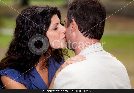 Kiss stock photo, A woman giving a man a kiss on the cheek by Tyler Olson