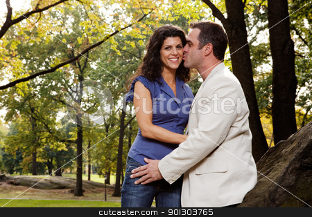 Park Kiss stock photo, A man kissing his girlfriend / wife in the park by Tyler Olson